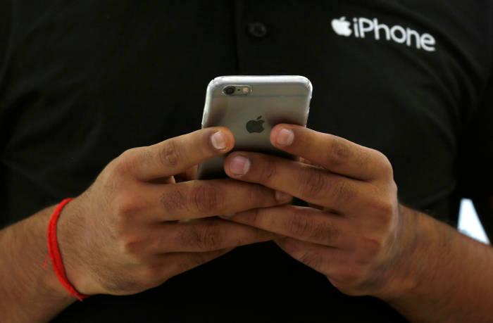 Seorang pegawai Apple Store sedang menggunakan iPhone