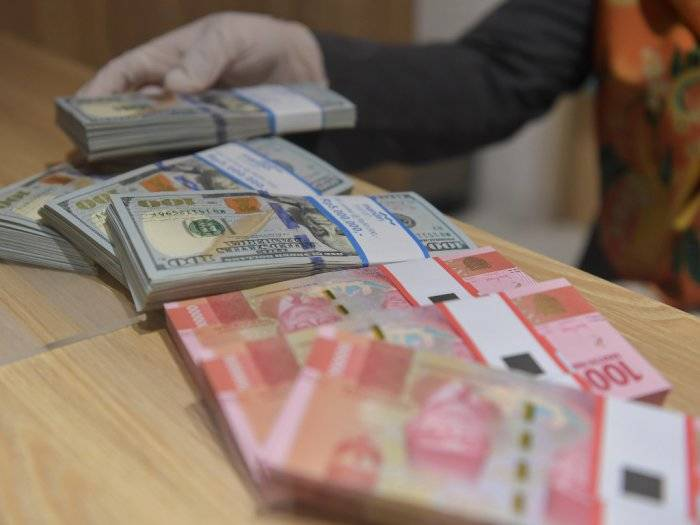 Ilustrasi karyawan menghitung uang rupiah dan dolar AS di Bank Mandiri Syariah, Jakarta, Senin (20/4/2020). (ANTARA FOTO/Nova Wahyudi)