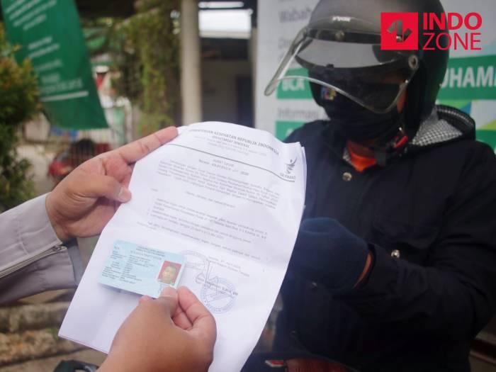 Petugas memeriksa kelengkapan Surat Izin Keluar Masuk (SIKM) Jakarta di Cek Poin PSBB Lampiri, Kalimalang, Jakarta, Selasa (26/5/2020). (INDOZONE/Febio Hernanto)