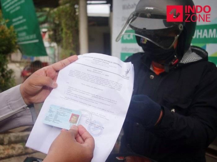 Petugas memeriksa kelengkapan Surat Izin Keluar Masuk (SIKM) Jakarta di Cek Poin PSBB Lampiri, Kalimalang, Jakarta.