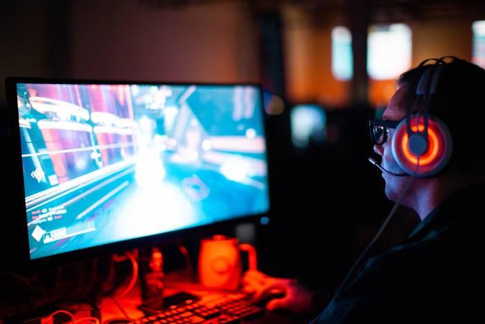 Ilustrasi seorang pria sedang bermain game di komputer