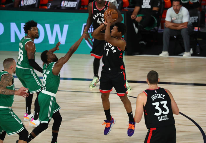 Guard Toronto Raptors Kyle Lowry (7) menembak melawan guard Boston Celtics Kemba Walker (8)