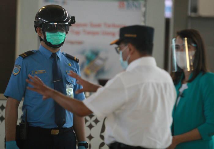 Menteri Perhubungan Budi Karya Sumadi (tengah) berbincang dengan petugas Avsec yang mengenakan helm pintar pendeteksi suhu tubuh