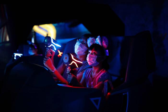 Pengunjung memakai masker wajah saat bermain di wahana