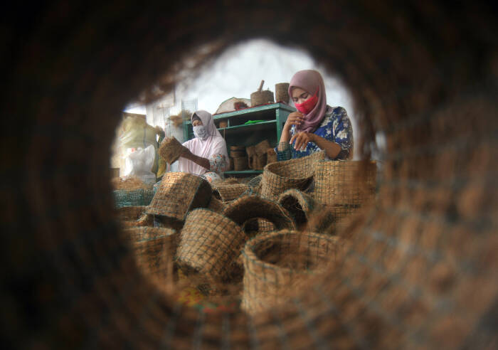 Perajin mengerjakan pembuatan pot bunga dari sabut kelapa
