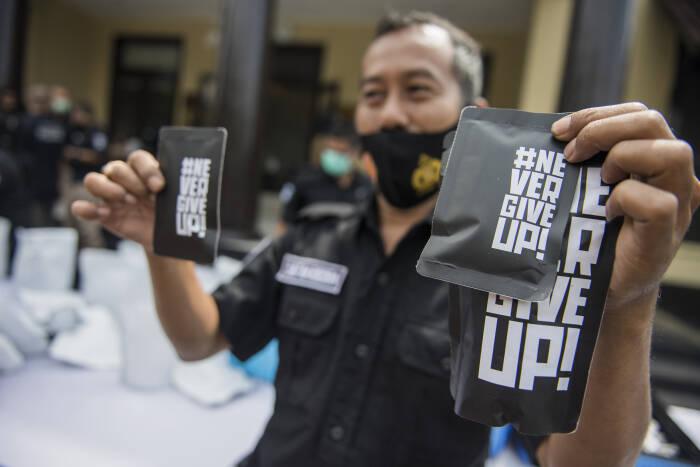 Anggota kepolisian Sat Reserse Narkoba Polrestabes Bandung menunjukan barang bukti tembakau sintesis (tembakau gorila) dalam kemasan siap edar