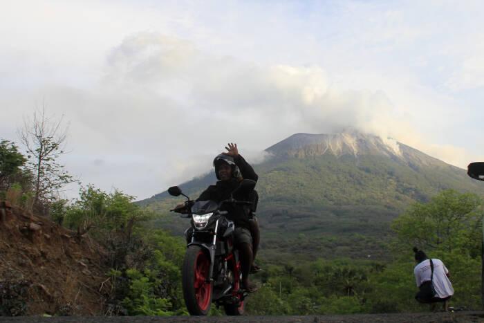 Seorang pengendara bermotor melaju dengan latar belakang gunung Ili Lewotolok