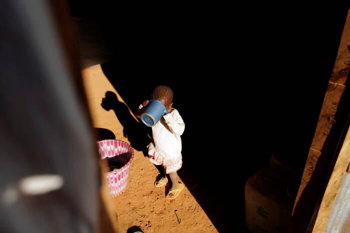Seorang gadis yang melarikan diri bersama orang tuanya dari serangan militan bersenjata di wilayah Sahel meminum air di tendanya